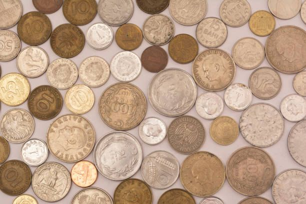 old turkish liras and foreign coins on isolated white texture