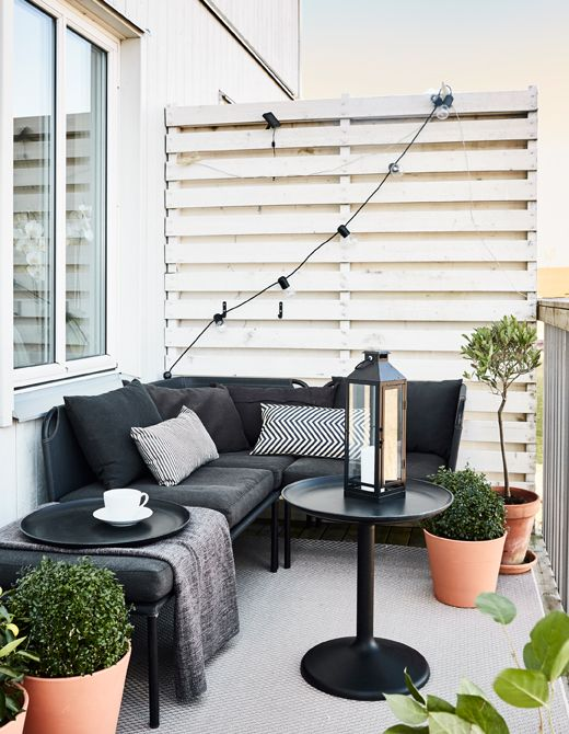 An outdoor space is furnished with neutral coloured furniture, including a sofa, coffee table, and rug.