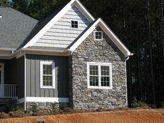 Dark blue/grey vinyl, vertical clapboard siding on a house with stone veneer around perimeter