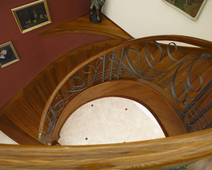 www.trabczynski.com ST455 Policzkowe schody gięte na wylewce betonowej wykonane z jesionu termowanego. Ręcznie kute stalowe balustrady z pochwytami drewnianymi. Słup wejściowy odlewany z brązu. Realizacja wykonana w prywatnej rezydencji , projekt – TRĄBCZYŃSKI / ST455Curved concrete stair clad with thermo ash wood. Hand-wrought steel balustrades with wooden handrails. Entrance newel post cast of bronze. Private residential project, designed by TRABCZYNSKI