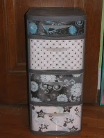 Modge-podging scrapbooking paper to make those cheap see-through drawers look a little nicer. Neat idea.  :)