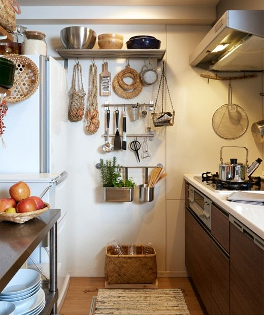 a narrow kitchen with dark cabinets and utensils hanging on metal rh in pinterest com