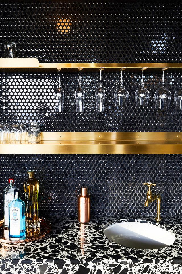 GRT Architects  A dark tile backsplash sets the mood for evening entertaining, particularly when your definition of following a recipe involves mixing a cocktail rather than making a meal. In this kitchen, the chic metallic shelves and bar-top accents are narrowly outshone by the sleek, glossy finish on the black penny tiles.