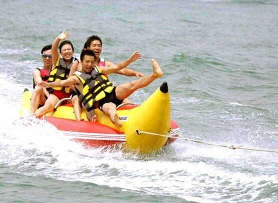 inflatable banana boat  3 people playing on the beach surf riding water game water toys