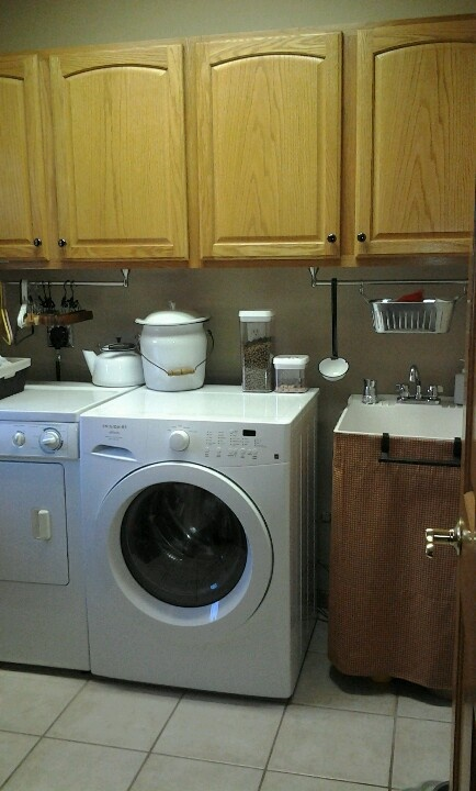 laundry room mini makeover installed towel rods under the upper cabinets for empty hanger storage
