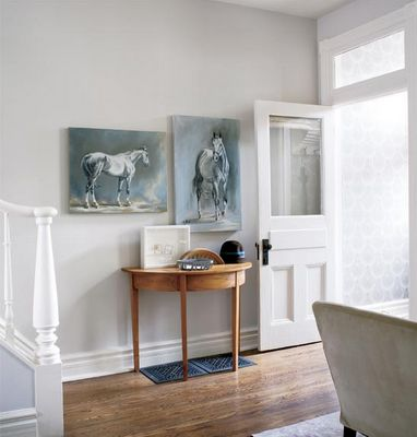 Style at Home editor Erin McLaughlin has also incorporated her love for horses in her home's interior design. The dreamy portraits of her Oldenburg-cross gelding by artist friend Jenn Pratt are hung in her simple, but elegant entry.