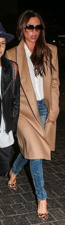 Who made Victoria Beckham's tan coat, white button down shirt, black sunglasses, and blue skinny jeans?