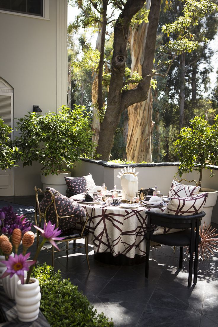 Contemporary Eclectic Tablescape: An outdoor dining table surrounded by chairs.