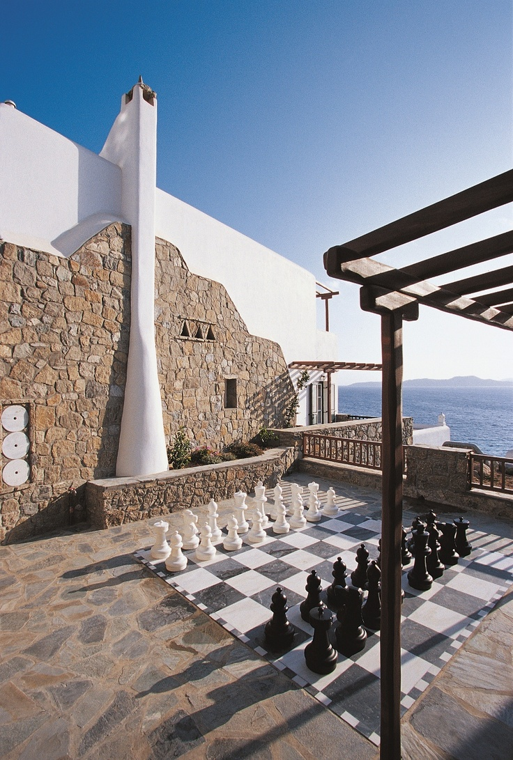 Mykonos Grand Luxury Hotel Chess area on marble slabs with Cycladic chimney and wooden pergola
