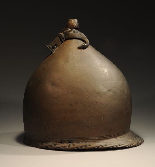 "ETRUSCO-ROMAN BRONZE HELMET  of the ""jockey cap"" type, featuring an elegant domed form with a circular knob, incised decoration around the rim and on projecting rear neck guard. Tiber patina. This was a helmet type used by soldiers in the Roman Republican army. This type of helmet derives from Celtic types and was in use from the late 4th through the 2nd centuries B.C."