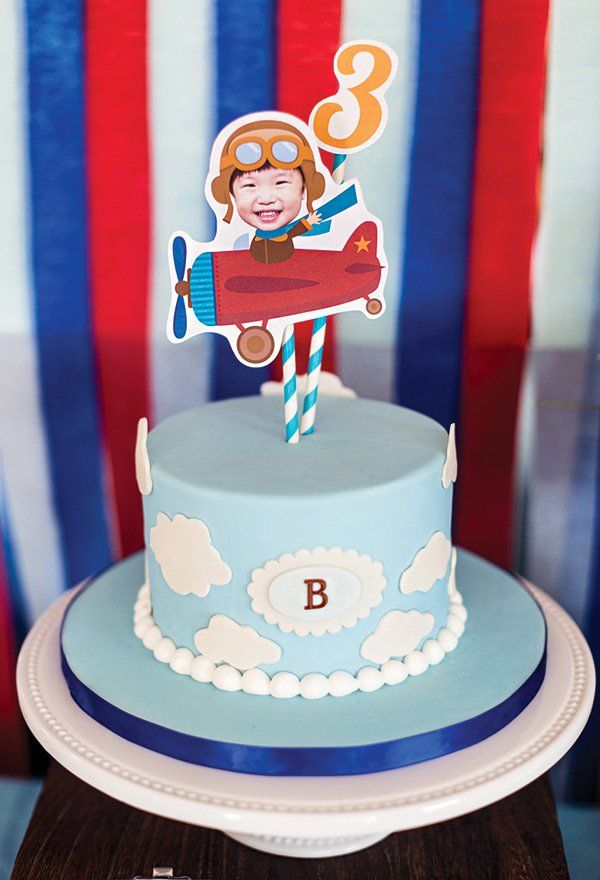 An airplane birthday party with paper airplanes, a map backdrop, cloud birthday cake, in flight peanuts, 'jet fuel' drinks + chocolate chip cookie favors