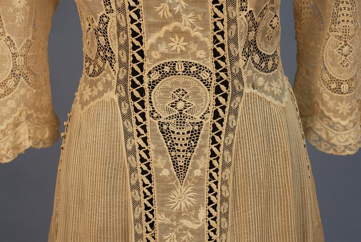 TRAINED LACE on NET HIGH NECK GOWN, c. 1904. 2-piece cream net with 3/4 balloon sleeve, floral applique lace with cloverleaf lattice over boned silk bodice, chiffon under skirt with pleated hem ruffle, silk lining.