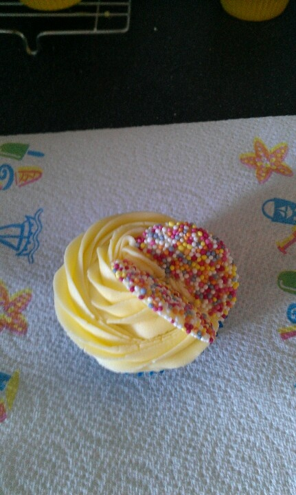 Vanilla cupcake with buttercream and giant smarties.