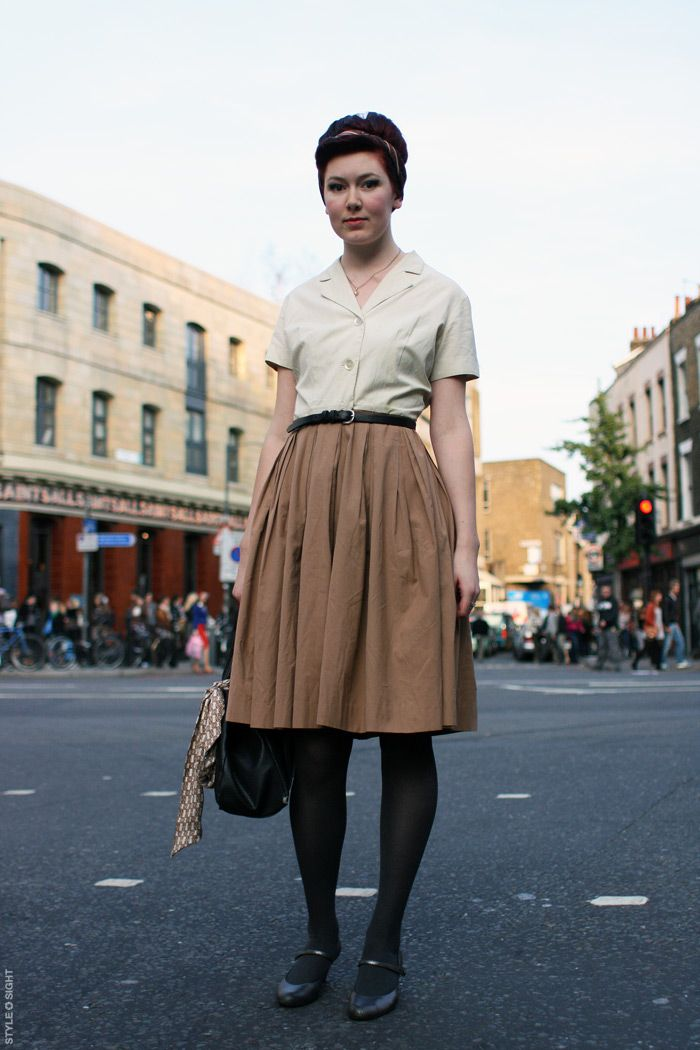 White short-sleeved blouse (tucked in), camel a-line skirt, black tights, black pointy flats