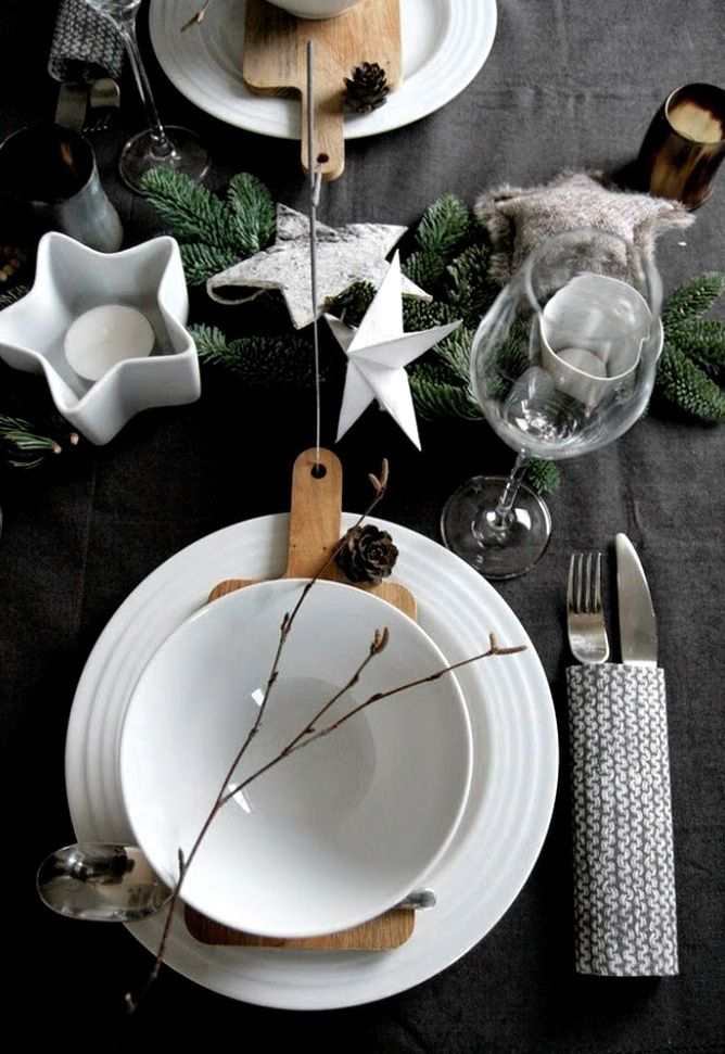 Dark contrasting grey table linens with white crockery and warm wood in this Christmas table setting