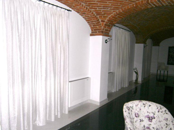 Tende bianche con bastoni in ferro battuto, complemento perfetto per un ambiente rustico