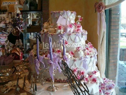 http://www.lemienozze.it/operatori-matrimonio/bomboniere/bomboniere-nozze-roma/media/foto/6  Sacchetti porta confetti sulla torta nuziale