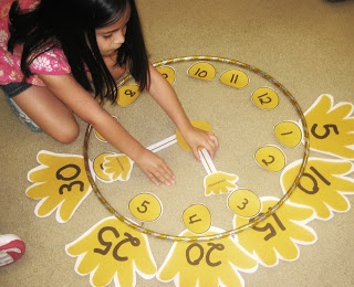 Then it was time to make a giant clock together. We used hula hoops for the face of the clock and cut out numbers and hands. We arranged all the pieces and practiced telling time to the hour as a group.