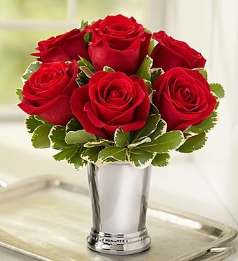 "Here's a gift that proves big things come in small packages! Beautifully designed as a stylish compact arrangement by our expert florists, it gathers six fresh, blooming roses in a shimmering julep cup vase that's perfect for brightening birthdays, romantic get-togethers or ""just because"" days. Just choose their favorite color—red, pink, yellow, lavender, white or a multicolored assortment—and get ready to make them smile."