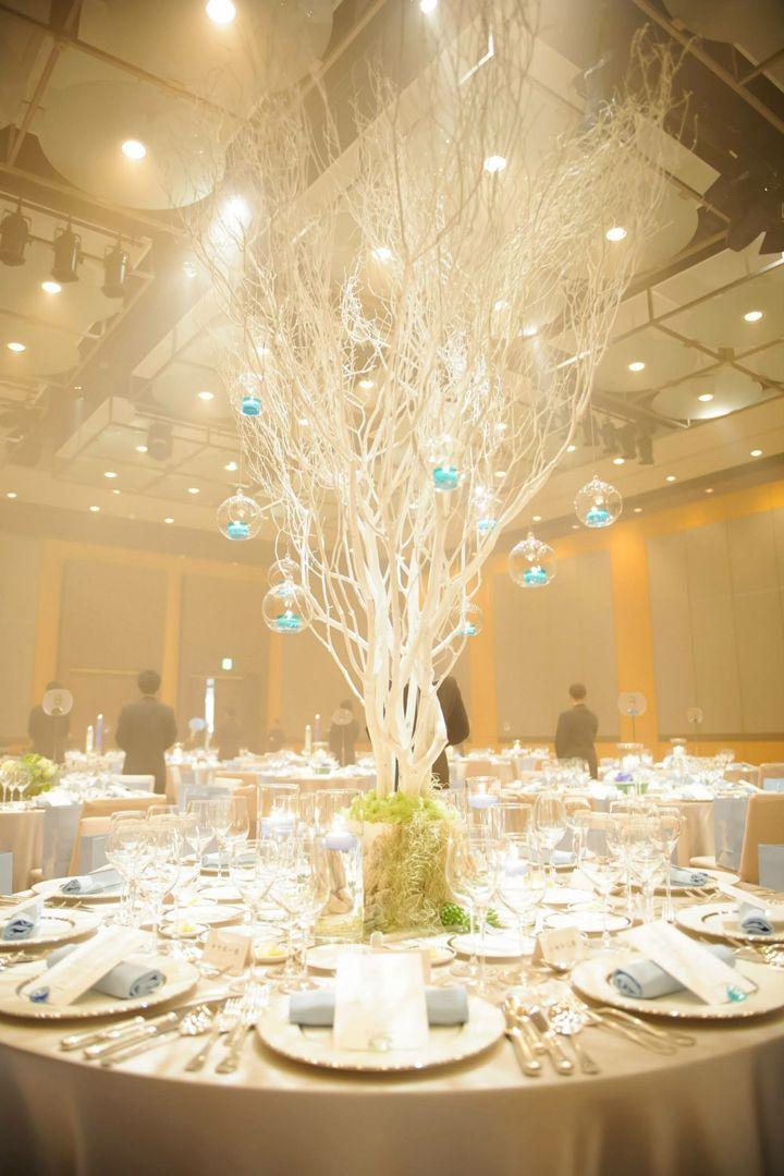 真っ白な砂浜をイメージさせる大きなホワイトツリーに、ブルーのキャンドルをつるすだけのシンプルなアレンジなのに、会場の印象は幻想的でまるで海の中の祝宴のよう。