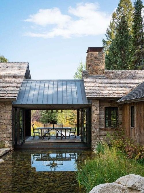 Establishing a breeze way between two common areas of your home and mixing that with a run off pond. See the aluminium roof...it probably collects the rain water and deposits into the run off pond. Great idea! Cozy and oh...good idea!!