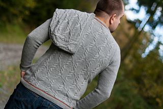 "The sweater is a top down seamlessly knitted man henley sweater, with some unique details like herringbone stripes in contrasting color in hems and button band, stylish buttons of your choice, and masculine cabling knitted at the back of the sweater, which is an answer to both his needs to have a ""simple"" sweater without too much decoration, and hers needs to knit a sweater which is nice and interesting knitting journey."