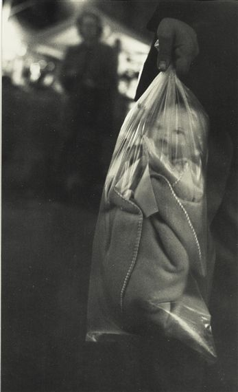 Robert Frank -- Robert Franks photograph seems normal at first, he captures everyday things for the most part, but this image doesnt seem so the more you look at it.. You see a baby in a plastic bag. Which at first makes the image feel very dark, then when you realise its fake you don't know whether to laugh.