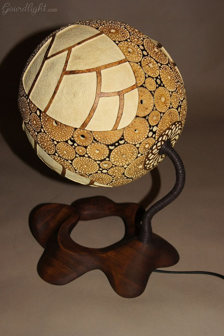 https://flic.kr/p/jDiwnt | Table lamp IX | Head of the lamp is made of Senegalese calabash. White parts are carved layer of the fruit which change the color to red/orange when the lamp is switched on. On the bottom of the lamp there's perforated closing part locked by magnets. The lamp was painted with wood oil and alcohol ink. Black parts are burnt calabash surface. The center element is genuine Baltic amber- ranked as the world's finest;  resin from the ancient trees dating back ~40…