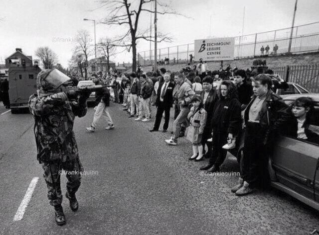 British Soldier takes aim at innocent civilians while walking past them in the north of Ireland. Late 1980s/Early 1990s