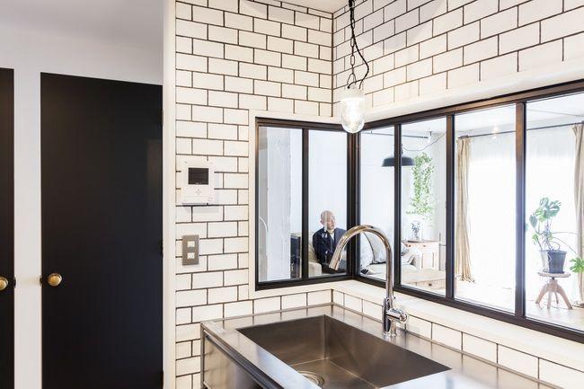キッチンとリビングを窓でつなぐ  白を基調としたキッチンはサブウェイタイルとフレームでスタイリッシュに