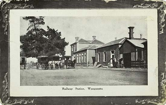 Wangaratta Railway Station, circa 1920. Inscription: Railway Station, Wangaratta. Description: Four horse drawn vehicles outside Wangaratta railway station. There appears to be a man with a child on the right. Location: Wangaratta, Victoria, Australia Date: circa 1920
