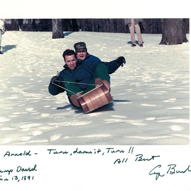 Arnold Schwarzenegger goes sledding with then president, George Bush, 1991