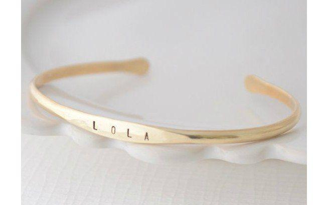 Finos braceletes dourados podem ter o nome do filho gravado. Fica discreto e elegante. De Etsy