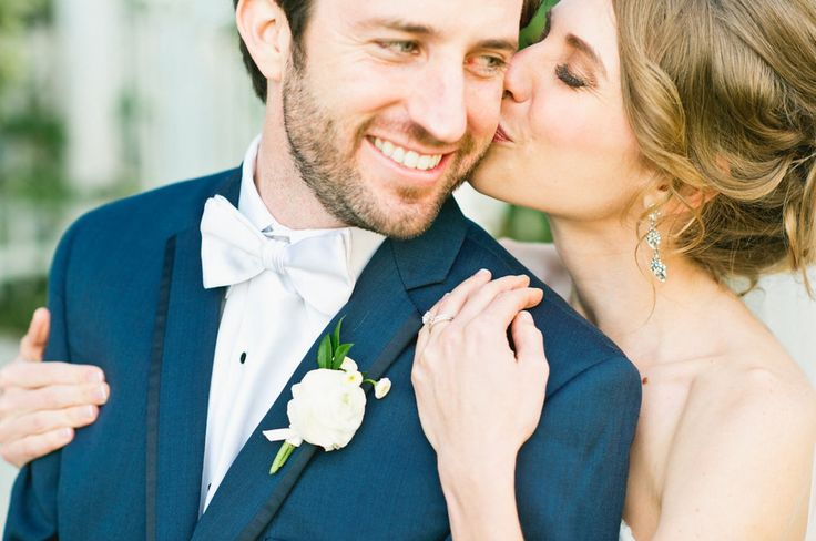 the groom gets a kiss from his new bride wearing a boutonniere of white ranunculus and button chamomile, wrapped in cream satin ribbon