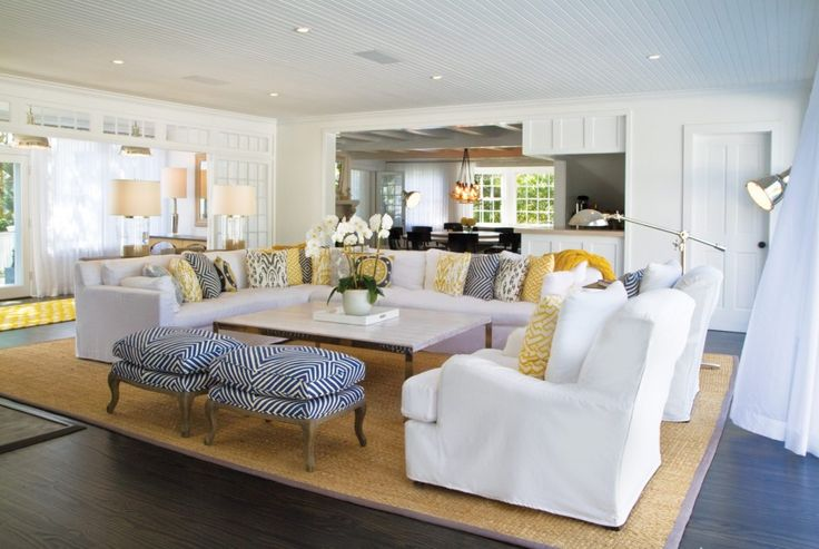 Living Room, Laminated Wood Flooring L Shaped White Fabric Sofa White Fabric Arm Chairs Patterned Pouffes  Multi Colored Cushions Rattan Area Rug Three Metal Floor Lamps White Flower Vase Simple Square Coffee Table Modern Table Lamps: Appealing Beach Cottage Decoration - Nautical Living Room Design Concept