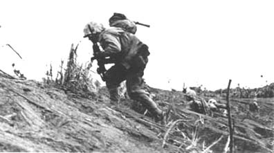 (left) Iwo Jima–1945. An infantry Marine moves out under fire across the badlands on the northern sector of the island.  On Iwo Jima, the 3rd MarDiv suffered 1,131 Marines killed and 4,438 Marines wounded in action.