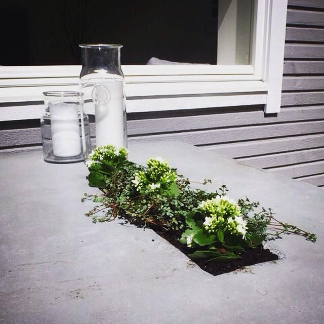 Utebord med blomsterkasse i midten.