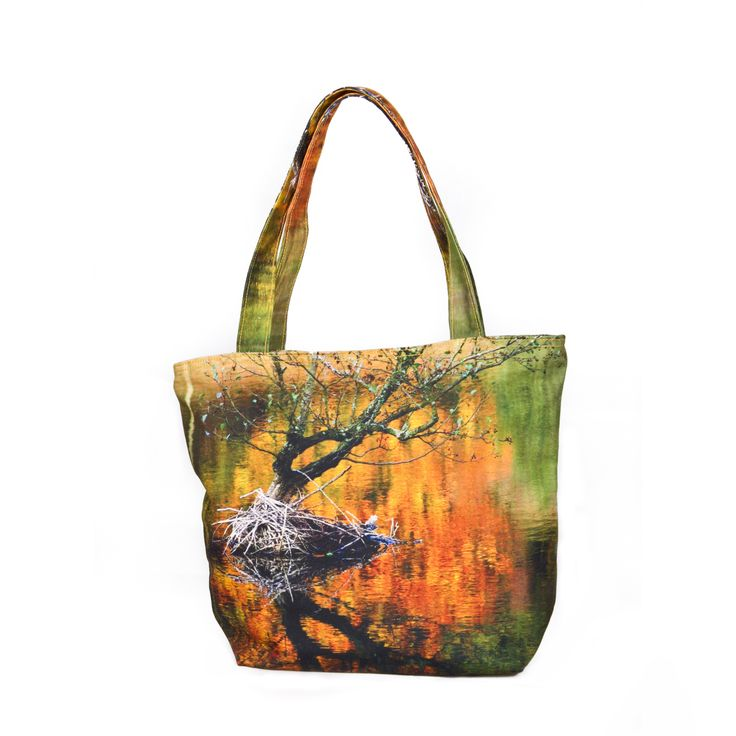 Fall in Mortemer, France    This bag depicts an image of a lone tree isolated in the water. Despite the simplicity of the tree itself, the overall look from the reflections give the bag a more alluring aspect; providing a nice piece for that autumn season when walking about on the streets. The blurred out background of the autumn foliage gives a nice contrasting factor to emphasize the beauty of the tree and its almost bare branches.