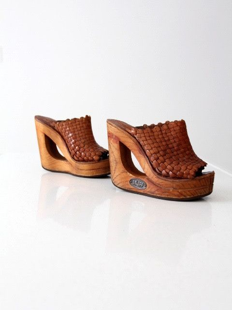 This is a pair of 1970s vintage Shoes n Stuff by Frank Sbicca platforms. Beautifully aged, basket weave brown leather shapes the top of the mules. They have a bold wood platform heel with a cut-out de