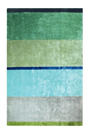 heavy, dense, and with a lustrous sheen, the hand-tufted eri rug makes a sophisticated display of the palette of the moment, sparkling emeralds, jades and aquas interplaying in tonal bands to wonderful effect.