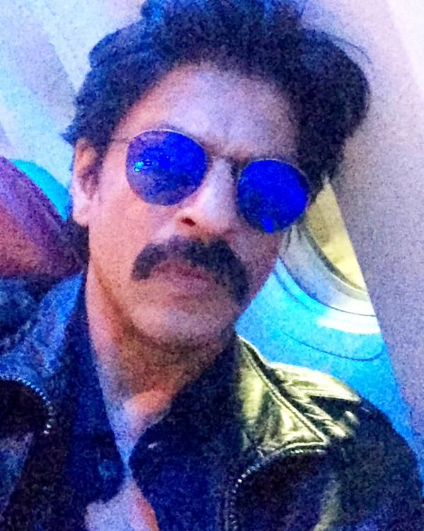"""#LatestUp We know that Shah Rukh Khan is sporting a full grown beard and moustache for his upcoming action thriller, Raees, where he will be seen essaying the role of a #gangster.   Keeping a part of his look intact, while he got rid of his beard, he's sticking with the #moustache for the time being and rocking it as well.  The actor tweeted:  """"Battery died on trimmer so part of Raees still on face."""" the man sure has his sense of humor in place! :D"""