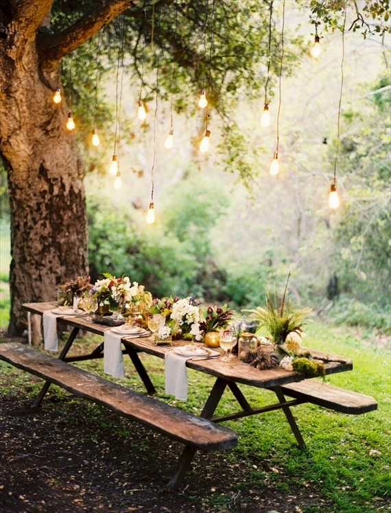 Picnic tables and industrial bulb hanging lights for outdoor woodsy wedding