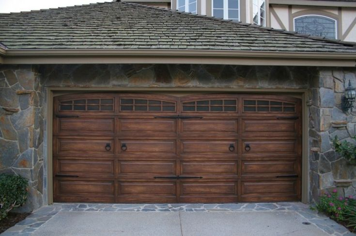 Dark Wooden Garage Arched Garage Door Stone Siding Grey