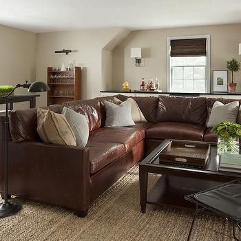 Neutral Family Room With Brown Leather Sectional Dotted Gray Striped Pillows And Linen Across From An Espresso Coffee Table Glass
