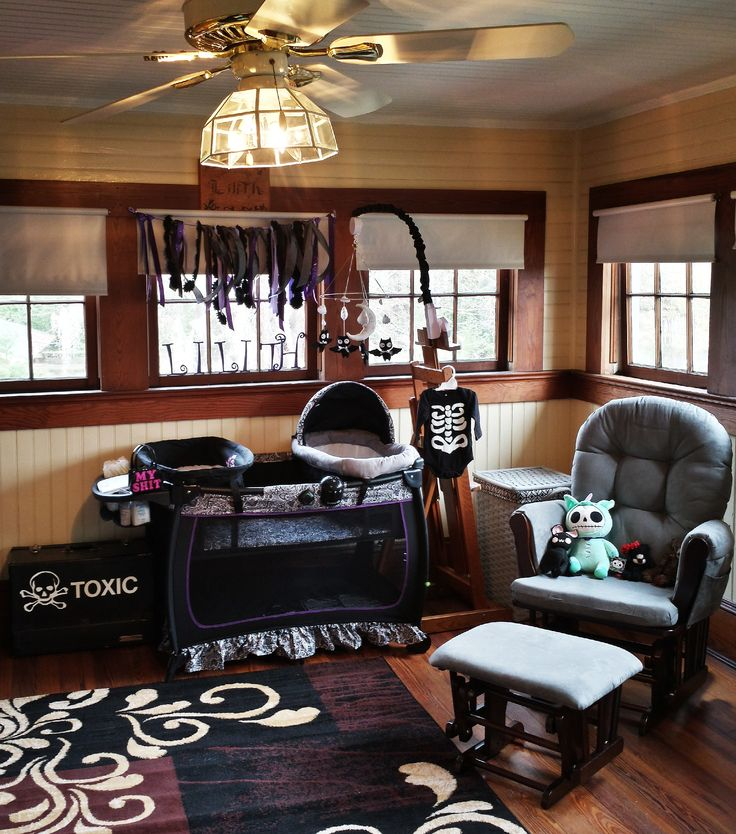 Goth style dark baby nursery / child room. cozy and medium lit. Black bassinet bed placard, bat baby mobile , rocking gliding chair skeleton outfit victorian room