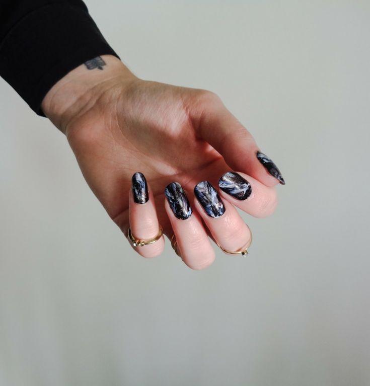 Unghie a mandorla effetto marmo con base nera, decorazioni unghie, tatuaggio polso