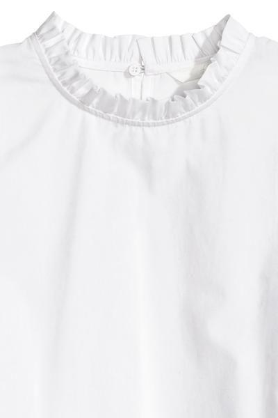 Camicetta cotone con volant: Camicetta in tessuto di cotone con piccolo volant sullo scollo. Apertura con bottone nascosto sulla nuca. Polsini con bordino a volant e bottone. Spacchetti laterali. Leggermente più lunga dietro.