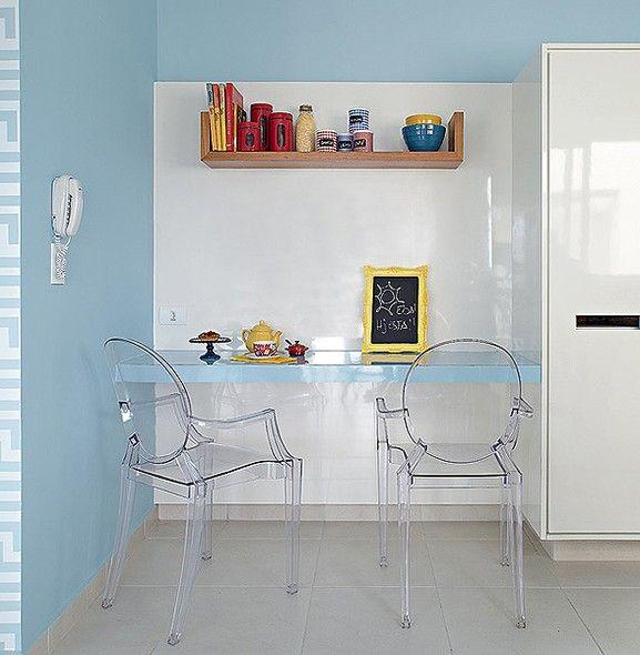 O cantinho para pequenas refeições, localizada na cozinha, tem prateleiras azuis, do mesmo tom da parede. Projeto da arquiteta Andrea Murao