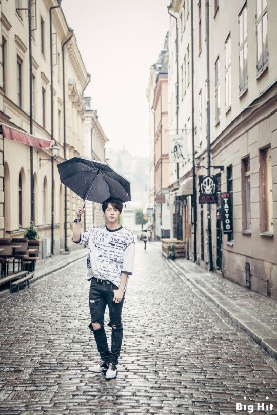 """[BTS in Sweden: Mischievous boys in Europe] - JIN Date: July 30th 2014 Location: Gamla Stan, Stockholm """"Those became magazine photos thanks to the beautiful streets although we took them roughly. Whenever sitting on the steps, leaning against the wall, and just walking on the street, they made pictorial photos! Because of the sudden rain during the  shooting, they got embarrassed but soon posed naturally with umbrella."""""""