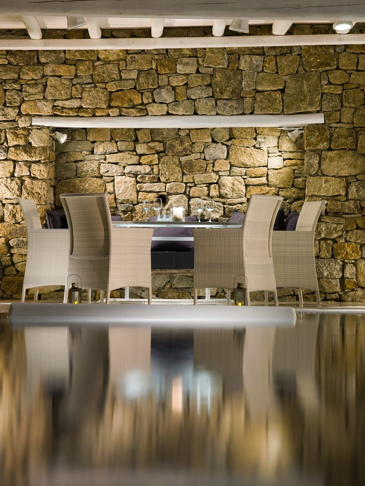 Detailed stone wall under the shade of a traditional wooden pergola, reflecting on the pool water. From Grand Suite with private pool of Mykonos Grand Luxury Hotel